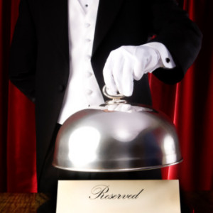 Maitre d' holding silver domed dish with reserved sign